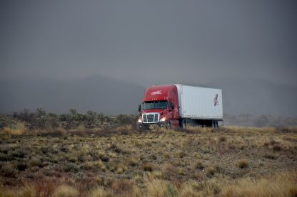 An image of a dry van on a desert road. Used to represent our standard ground, Turckload, Less-Than-Truckload training.